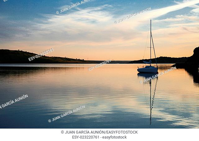 Sailboat anchored in the middle of Alange Reservoir, Spain. Sunset hour