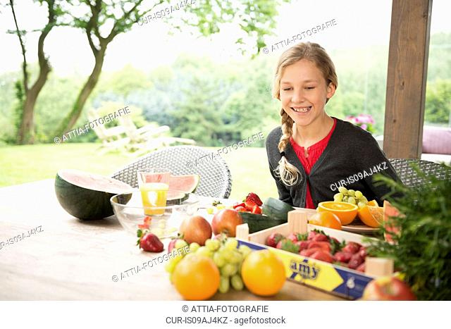 Girl at patio table with a variety of fresh fruit