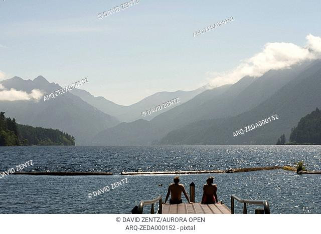 A couple sits on the end of a dock overlooking Lake Crescent in Olympic National Park, Washington on June 4, 2014