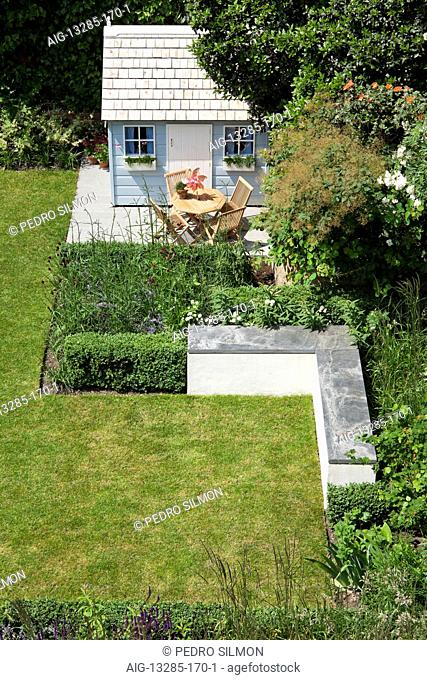 Lawn, playhouse and L-shaped bench in rear garden, North London, UK., designed by Modular. Photographed in June