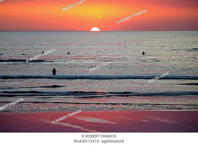 Surfers and swimmers at sunset off Playa Guiones beach, Nosara, Nicoya Peninsula, Guanacaste Province, Costa Rica, Central America