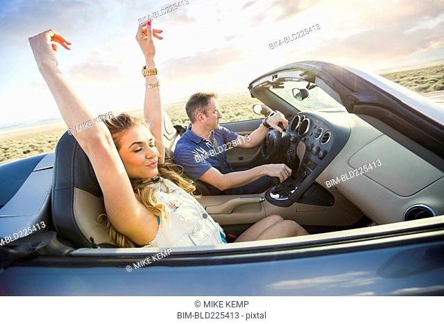Caucasian couple driving in sports car