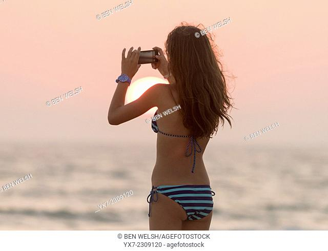 Teenager at the beach taking a photo of the sunset. Tarifa, Cadiz, Costa de la Luz, Andalusia, Spain