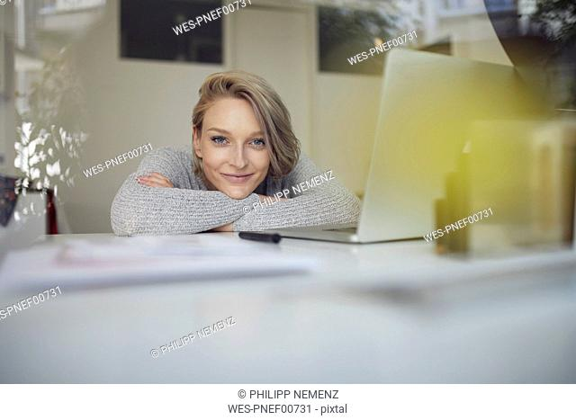 Portrait of smiling young woman leaning on desk with laptop