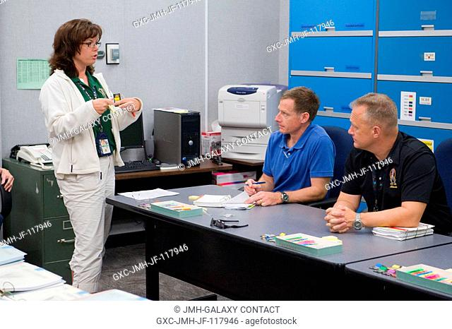 NASA astronauts Chris Ferguson (seated left), STS-135 commander; and Doug Hurley, pilot, participate in a flight data file review in the Flight Operations...