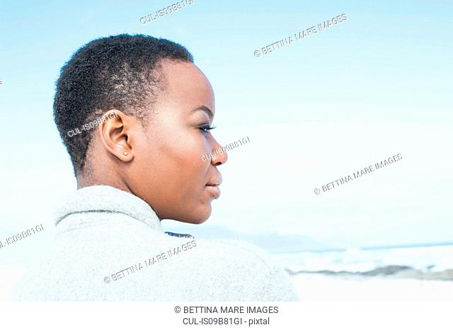 Young woman on beach, looking at view, pensive expression