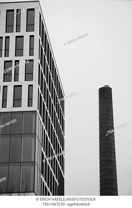 Old factory chimney next to a new office complex in Munich