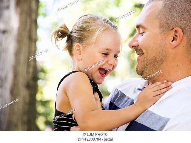 Father holding his daughter in park in autumn; Edmonton, Alberta, Canada