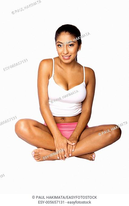 Beautiful Happy young woman wearing sporty white spaghetti strap top and pink shorts showing belly button sitting in lotus pose, on white