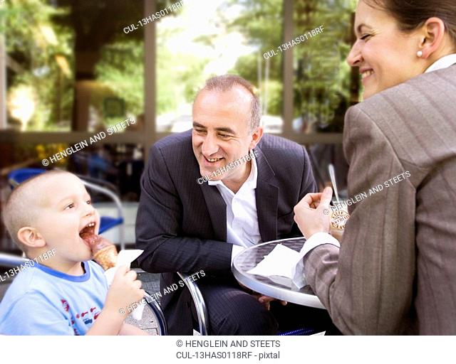 business couple with son in outdoor cafe