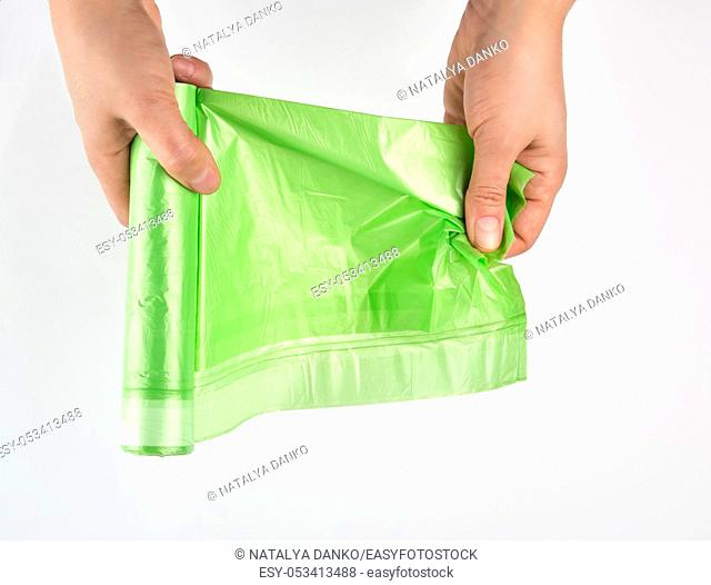 female hand unwind green roll with plastic bags for garbage on a white background, top view