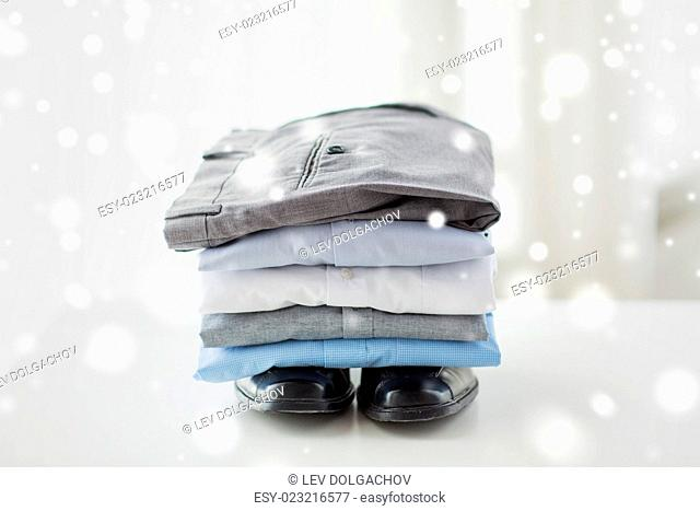 business, clothes, housekeeping and objects concept - close up of ironed and folded shirts, trousers and formal shoes on table at home over snow effect