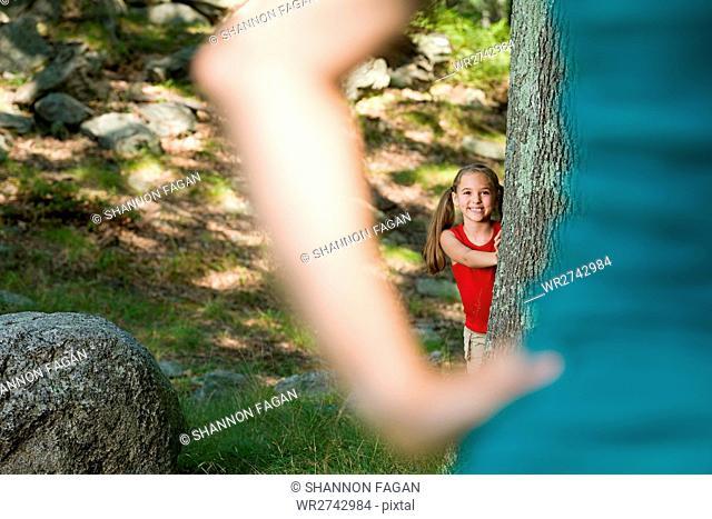 Girl hiding behind a tree