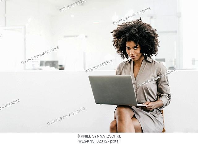 Young woman using laptop in office
