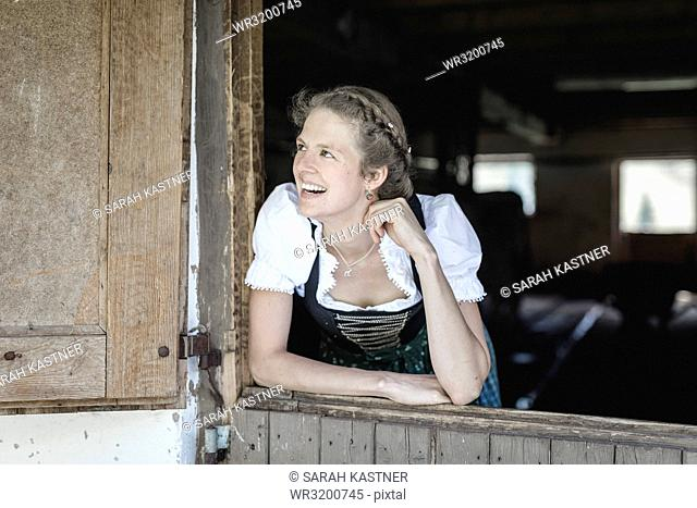 Countrywoman with dirndl looks out of a barn door