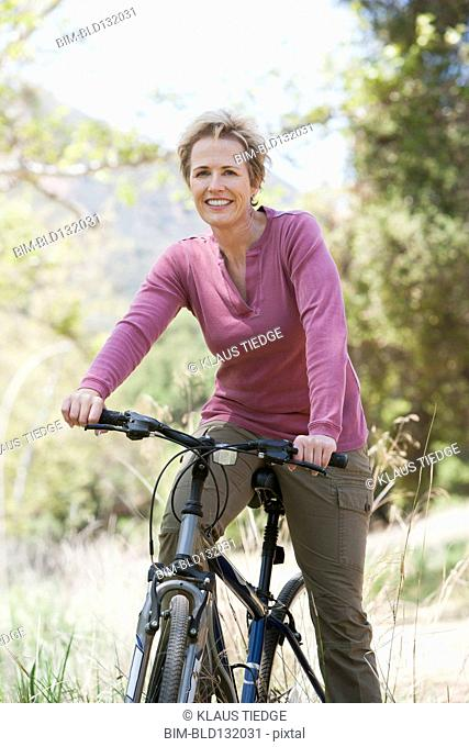 Senior Caucasian woman riding bicycle on rural path