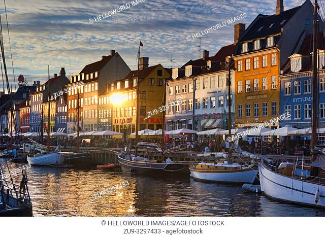 Nyhavn Canal wooden ships townhouses and alfresco terrace, Nyhavn, Copenhagen, Denmark, Scandinavia. 17th century waterfront district lined by brightly coloured...