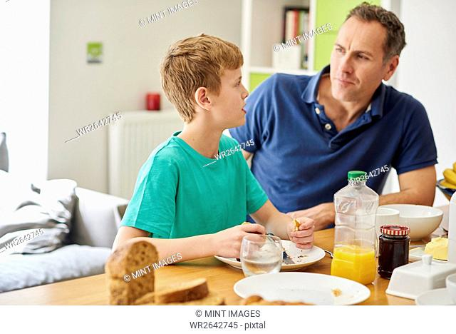 A father and son, man and boy sitting at the breakfast table