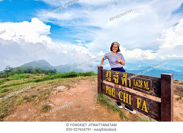 Tourist teen girl hiker wear cap and glasses standing smile pose thumb up near nameplate attractions of Phu Chi Fa Forest Park on mountain and blue sky...