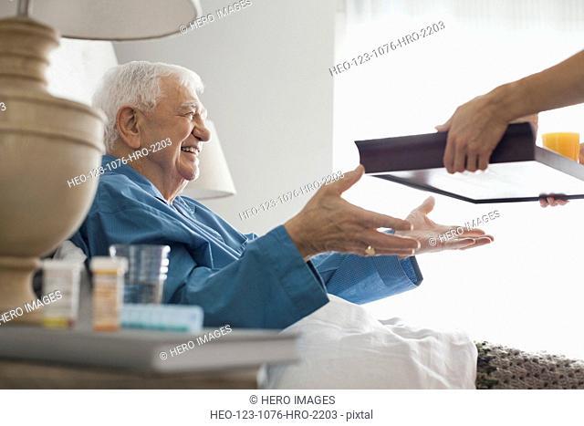 Senior man receiving breakfast tray from home care nurse