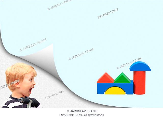 Surprised boy in an exposed corner is looking at blank blue page with a building of wooden cubes toys