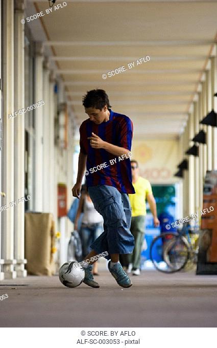 Teenage boy dribbling soccer ball in town