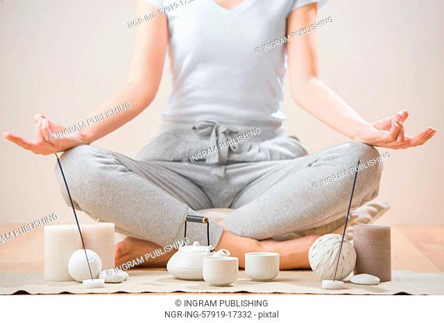 Yoga meditation at home. Relaxation concept with unrecognizable spiritual young woman sitting in front of candles, tea and aromatic sticks
