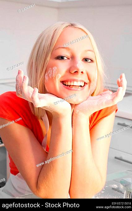 beautiful young woman making dough at home in the kitchen