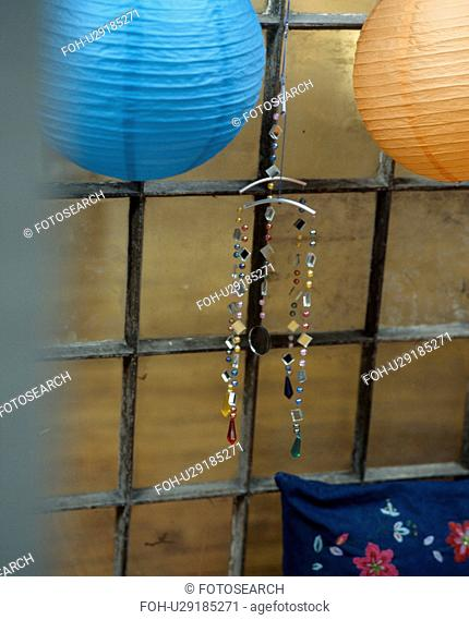 Close-up of turquoise and orange paper lampshades with jewelled ornament
