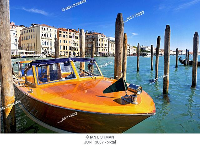 Wooden water taxi boat moored on sunny Grand Canal in front of architectural buildings in Venice, Italy