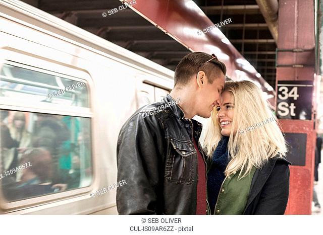 Romantic young couple on New York City subway platform, New York, USA