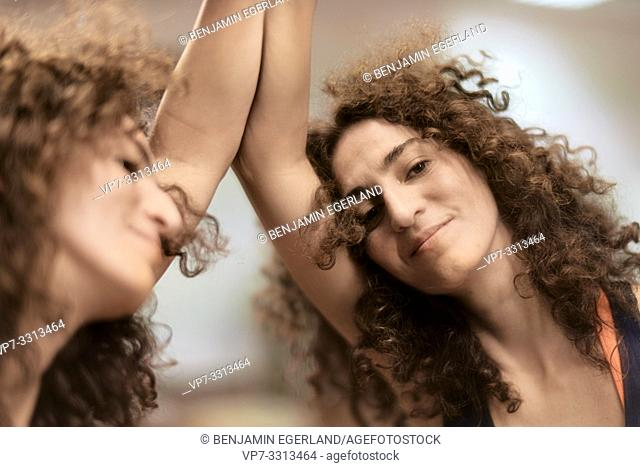 sporty woman leaning against mirror, mirror image, relaxed