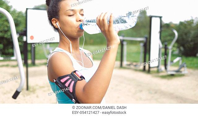 Beautiful ethnic woman in sportswear using smartphone and headphones and drinking water with eyes closed in park
