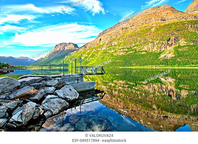 One boat dock by the sea in the morning. Colorful mountains reflecting from water surface