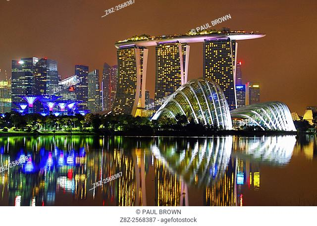 Night scene of the city skyline of Singapore showing the Flower Dome and Cloud Forest domes and Supertrees Grove in the Gardens by the Bay and the Marina Bay...