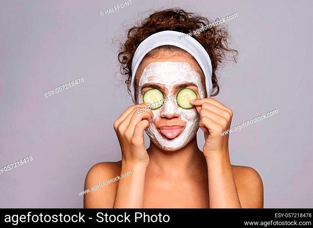 A portrait of a young woman with face mask and cucumber in a studio, beauty and skin care concept