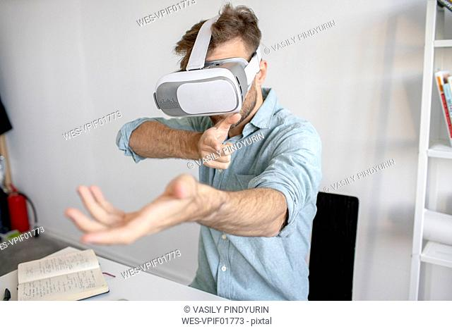 Man wearing VR glasses at desk in office