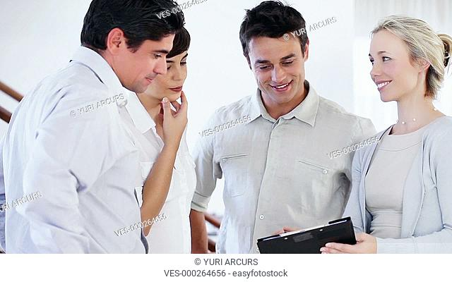 Group of four businesspeople having a conversation and smiling while one holds a clipboard