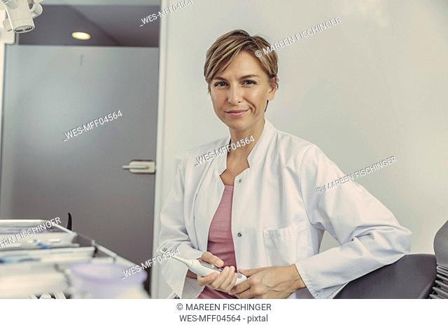 Female dentist holding electrical tooth brush