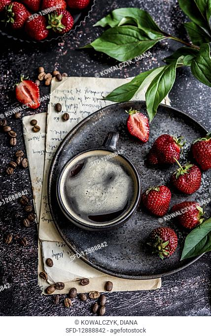 Cup of coffee on a serving plate, strawberries beside it