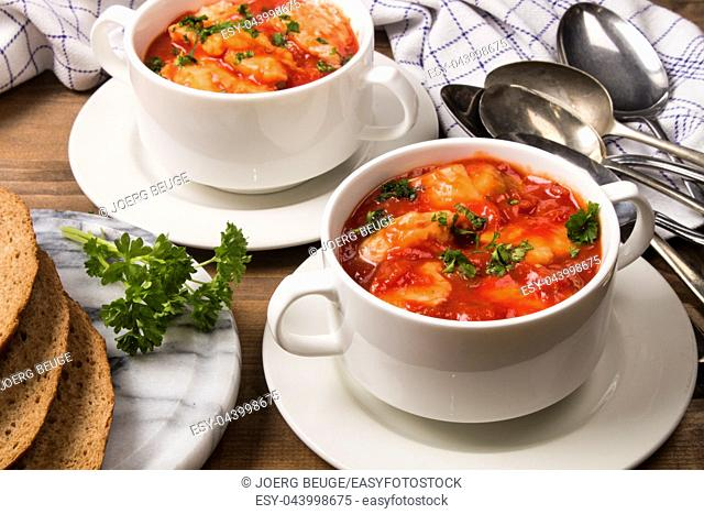 sea food mix soup in a white bowl with parsley