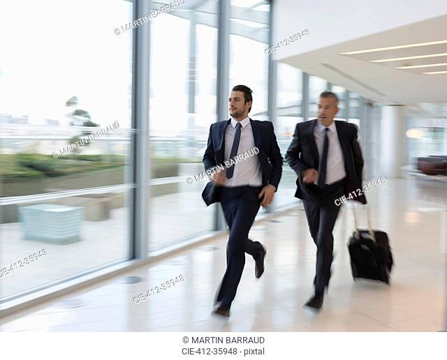 Businessmen running, rushing with suitcase in airport