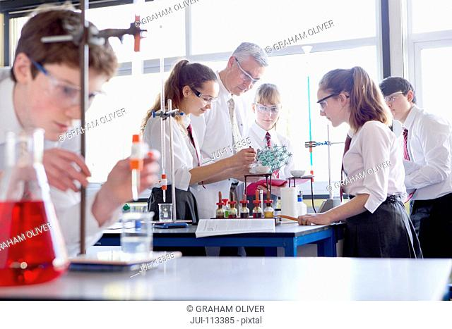Chemistry teacher guiding high school students conducting scientific experiment