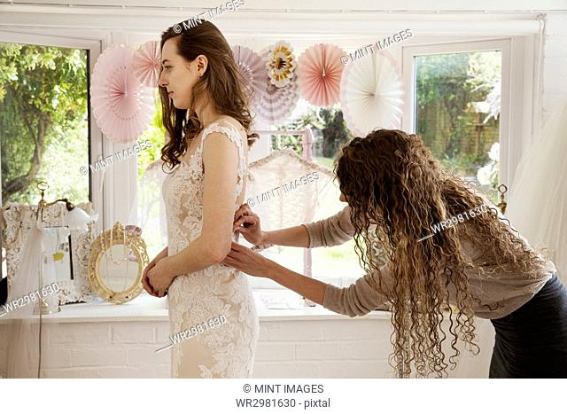 A dressmaker taking in a wedding dress, pinning and fitting it to the client, a young woman. A bride selecting her dress in a specialist shop