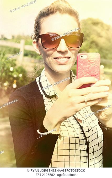 Vintage photograph of a young woman holding modern cell phone taking picture in rural park location. Technology lifestyle