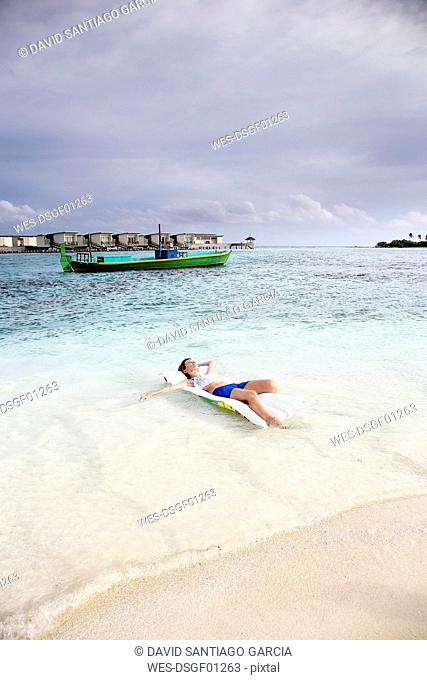 Maldives, Guraidhoo, woman floating on airbed in shallow water