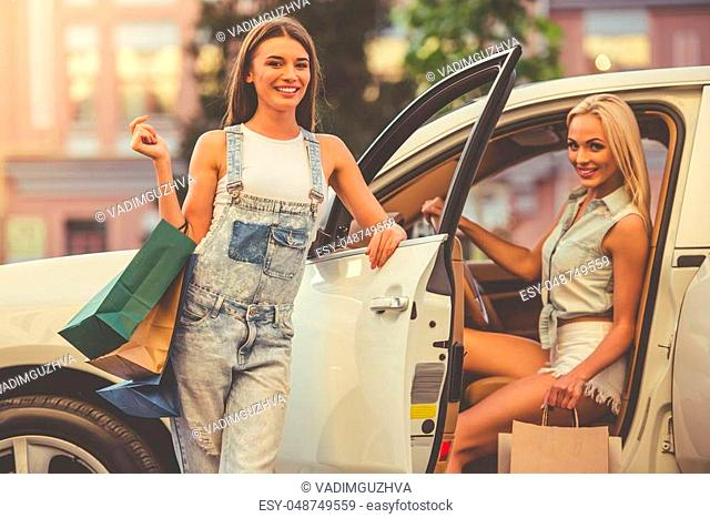 Beautiful stylish girls are holding shopping bags, looking at camera and smiling while standing near their car outdoors