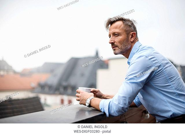 Portrait of mature businessman with cup of coffee on roof terrace