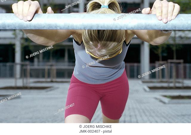 A young athletic woman, 15-20 20-25 25-30 years old, blond, sporty, stretching