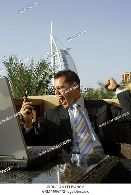 Triumphing businessman with mobile phone in Dubai (Burj Al Arab hotel in background)